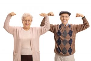 Joyful seniors flexing their biceps and looking at the camera isolated on white background